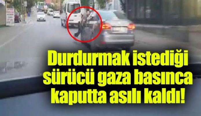 Durdurmak istediği sürücü gaza basınca kaputta asılı kaldı!